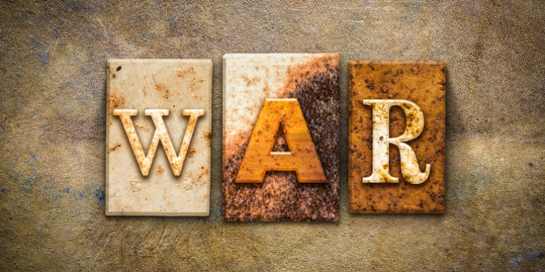 "The word ""WAR"" written in rusty metal letterpress type on an old aged leather background."